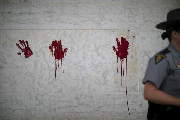 In this Thursday, June 18, 2020 photo, a small group of protestors placed painted red hands on the Ohio Statehouse, to signify the blood on police hands, they said during a demonstration in Columbus, Ohio. (Courtney Hergesheimer/The Columbus Dispatch via AP)