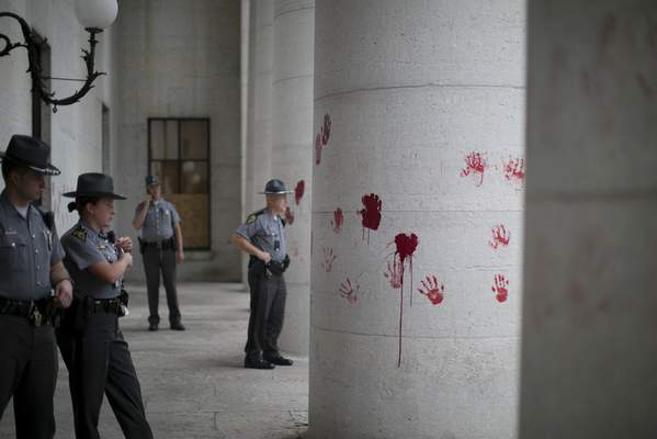 In this Thursday, June 18, 2020 photo, law enforcement stands in position after a small group of protesters placed painted red hands on the Ohio Statehouse, to signify the blood on police hands, they said during a demonstration in Columbus, Ohio. (Courtney Hergesheimer/The Columbus Dispatch via AP)