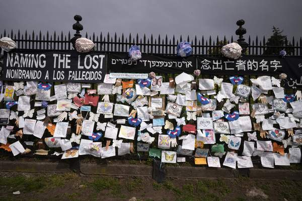 FILE - In this Thursday, May 28, 2020 file photo, a fence outside Brooklyn's Green-Wood Cemetery is adorned with tributes to victims of COVID-19 in New York. (AP Photo/Mark Lennihan)