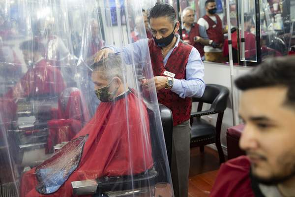 Associated Press A barber cuts the hair ofa customer at Ace of Cuts barbershopin New York City on Monday, the first day barbershops could reopen in the city.