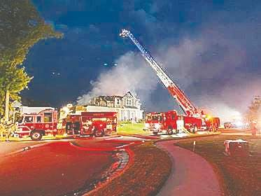 Courtesy photo Aboite Township firefighters work to put out a fireworks-related fire Sunday night.