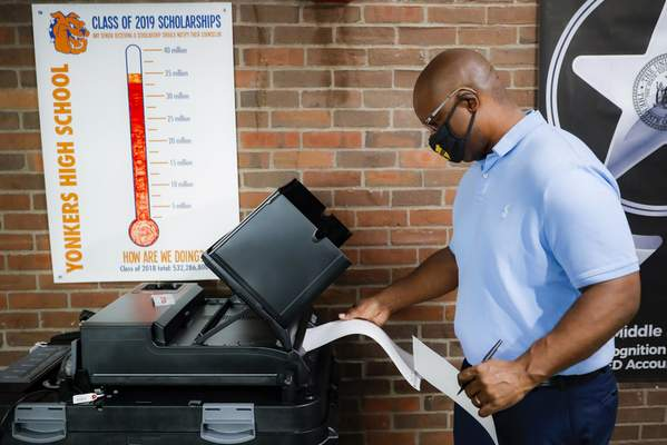 Jamaal Bowman votes at a polling station inside Yonkers Middle/High School, Tuesday, June 23, 2020, in Yonkers, N.Y. (AP Photo/John Minchillo)