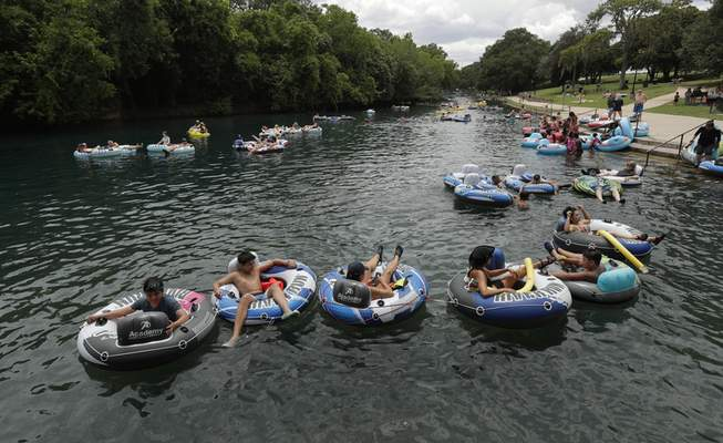 Tubers float the Comal River despite the recent spike in COVID-19 cases, Thursday, June 25, 2020, in New Braunfels, Texas. Texas Gov. Greg Abbott said Wednesday that the state is facing a massive outbreak in the coronavirus pandemic and that some new local restrictions may be needed to protect hospital space for new patients. (AP Photo/Eric Gay)