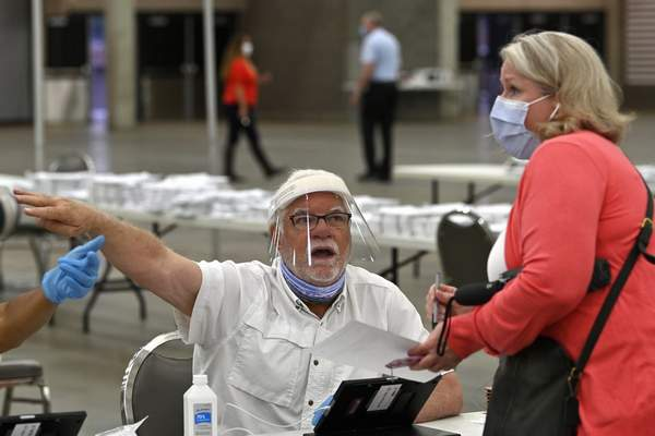 In this Tuesday, June 23, 2020 file photo, poll workers instruct a voter on where to go to fill out their ballot during the Kentucky primary at the Kentucky Exposition Center in Louisville, Ky. (AP Photo/Timothy D. Easley, File)