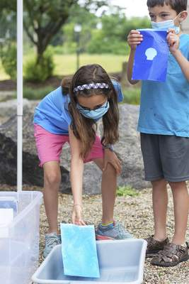 Katie Fyfe | The Journal Gazette  Nora Hanna, 9, and her brother Oliver Hanna, 7, create their own cyanotypes at Science Central on Saturday.