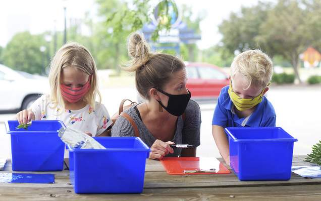 Katie Fyfe | The Journal Gazette  Evelyn Todia, 6, Amy Todia, and Eli Todia, 4, create their own cyanotypes during an outdoor program led by local artist and art teacher Erin Patton-McFarren at Science Central on Saturday.