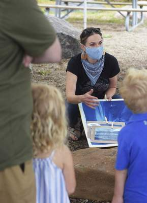 Katie Fyfe | The Journal Gazette  Local artist and art teacher Erin Patton-McFarren shows visitors cyanotypes she has made in the past during her program with Science Central on Saturday.