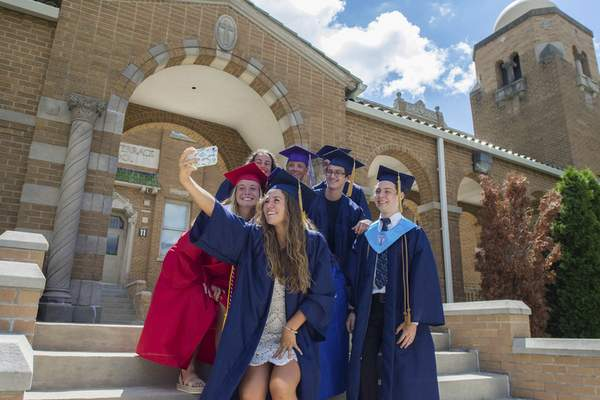 Michelle Davies | The Journal Gazette 2016 classmates of St. Jude's Catholic School, gather on the front steps of the scool for a 2020 high school graduation group selfie Wednesday afternoon.