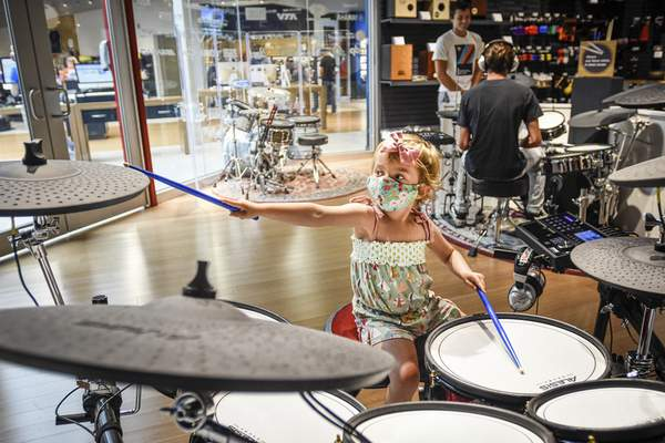 Mike Moore | The Journal Gazette Lucy Pizzolato, 4 jams out on Saturday while checking out the showroom at Sweetwater Sound with her father Dan Pizzolato.