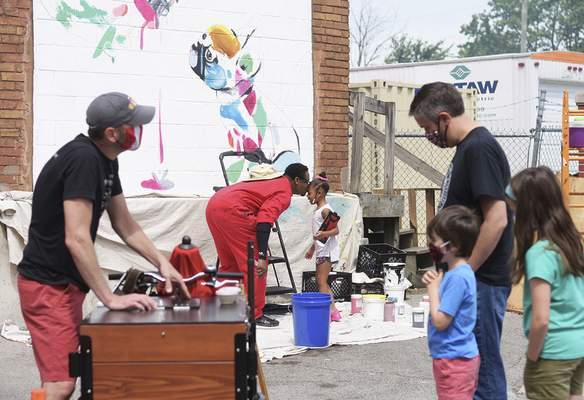 Katie Fyfe | The Journal Gazette Theoplis Smith takes a break from painting to visit his daughter MaKenna Smith, 4, while spectators order ice cream from West Central Microcreamery at 222 Pearl Street across from the landing on Friday, June 26th, 2020.