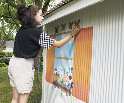 Michelle Davies | The Journal Gazette Jackeline Shackleford, 14, works on painting a mural on her neighbor's shed, Pat and Pamela Downs, Tuesday morning. Her sister, Alondra Shackleford, 16, also worked on the mural.