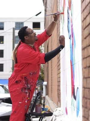 Katie Fyfe | The Journal Gazette Theoplis Smith paints the mural I SCREAM YOU SCREAM WE ALL SCREAM FORT WAYNE! at 222 Pearl Street across from the landing on Friday, June 26th, 2020.