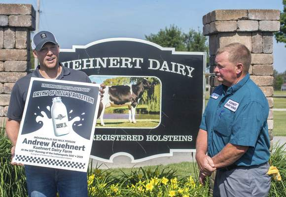 Michelle Davies | The Journal Gazette Al Kuehnert, right, listens as his son, Andrew Kuehnert, left, recounts his experience of being the Milk Man at the 2019 Indianapolis 500 Race. Kuehnert was given a commemorative sign from the American Dairy Association of Indiana, presented by Allie Rieth, Monday morning at the family dairy farm where Andrew is the farmer relations manager. Andrew Kuehnert said it was true honor to be the Milk Man and a part of history.