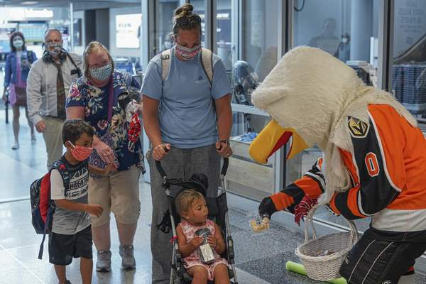Mike Moore | The Journal Gazette Icy D. Eagle, mascot of the Fort Wayne Komets Hockey Team, handed out the three millionth cookie on Friday to Passenger Holly Jones, along with her mother, Tara Vogel and two children, Trey Jones, 5 and Avery Jones, 2. The group was randomly selected as the lucky winner as passengers deplaned the arriving Tampa Bay/St. Petersburg flight on Allegiant Air. Holly was not only awarded the special cookie, but also received a gift basket full of gifts and goods from FWA, a voucher good for roundtrip airfare for two on Allegiant Air, and a supply of cookies from Ellison Bakery.