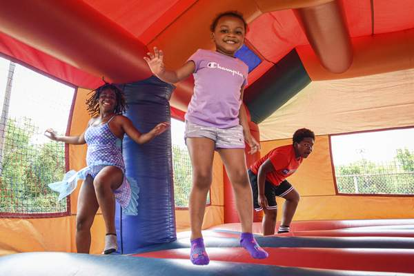 Mike Moore | The Journal Gazette Kids enjoy a bouncy castle on Saturday during the 2020 Youth and Community Celebration at Tillman Park.