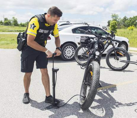 Michelle Davies | The Journal Gazette Officer Pedro Yaruchyk, with the Allen County Sheriff's Department, checks the tire pressure on his electric assist bike before heading out on patrol at Buckner Park Tuesday afternoon.