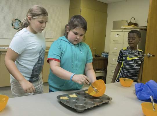 Michelle Davies | The Journal Gazette Addi Carey, 10, left, and Keshaun Stewart, 8, right, watch as Arianna Acker, 8, center, pours her egg muffin mixture into a pan Thursday morning during Cooking Class at the Fort Wayne Parks and Recreation Community Center.