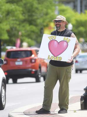 Katie Fyfe | The Journal Gazette Doug Ahr holds a sign reading You Are Loved to traffic along Jefferson Blvd. on Friday, June 26th, 2020. Ahr says he has been coming out almost everyday to send this positive message since March.