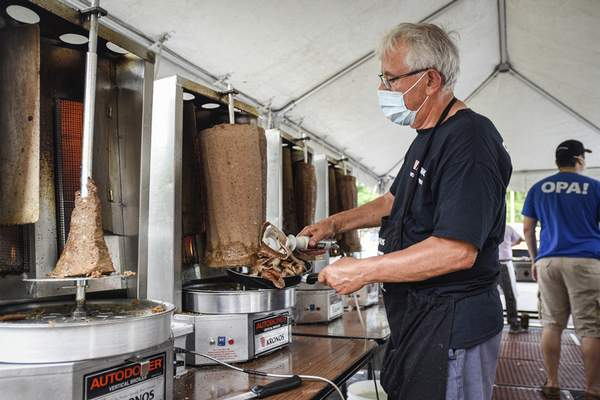 Mike Moore | The Journal Gazette Chris Naselaris volunteers his time on Saturday to shave gyro meat for curbside orders during Greek Fest at Holy Trinity Greek Orthodox Church on Wallen Road.