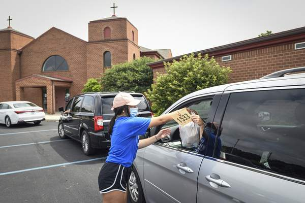 Mike Moore | The Journal Gazette Yianna Rongos delivers meals curbside on Saturday during the 40th anniversary of Greek Fest at the Holy Trinity Greek Orthodox Church on Wallen Road.