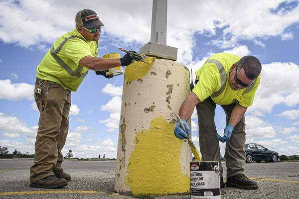 Mike Moore | The Journal Gazette Fort Wayne Parks and Recreation Department maintenance technicians Ed Stange, left and Joe Houser, apply a fresh coat of paint on Tuesday to pedestals in the parking lot at Kreager Park.