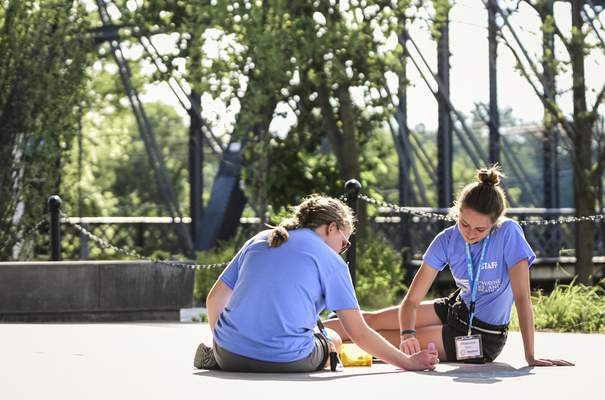 Mike Moore | The Journal Gazette Chalk It Up staff members Natalie Frazier, left and Rhiannon Freimuth decorate the patio with chalk under Promenade Park pavilion on Monday downtown.