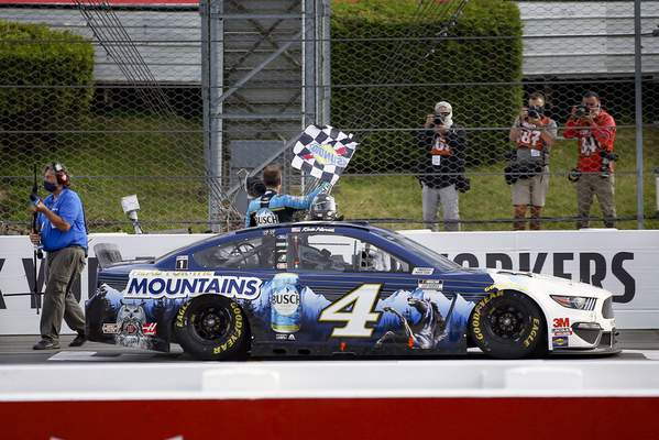 Associated Press Kevin Harvick waves a checkered flag for photographers after winning Saturday at Pocono Raceway in Long Pond, Pa.