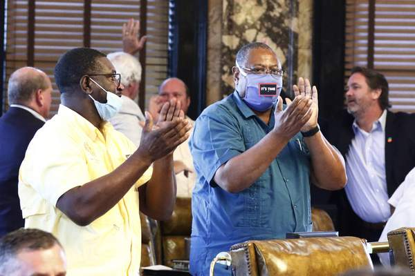 Associated Press Democratic Sens. Juan Barnett, left, and Robert Jackson applaud Saturday after the Mississippi Senate passed a resolution that would allow lawmakers to change the state flag.