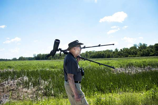 Katie Fyfe | The Journal Gazette Ed Powers carries a spotting scope with him for bird watching at the Eagle Marsh Nature Preserve on Thursday, June 11th, 2020.