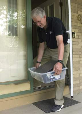 Michelle Davies | The Journal Gazette Duane Yoder of PC Doctor places a repaired monitor on the porch of his home for pickup, one of the adjustments he made for the pandemic.