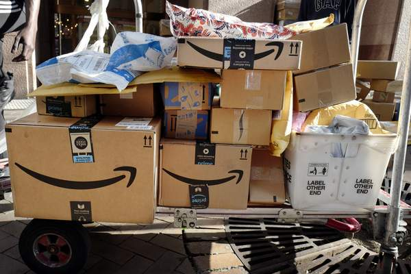 Associated Press  Amazon Prime boxes are loaded on a cart for delivery in New York. Amazon said Tuesday that its carbon footprint rose 15% last year.