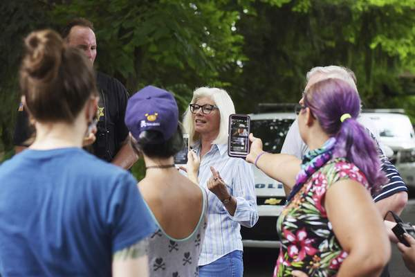 Katie Fyfe | The Journal Gazette  Allen County Prosecutor Karen Richards stands outside of her home to talk with protesters and answer questions on Sunday.
