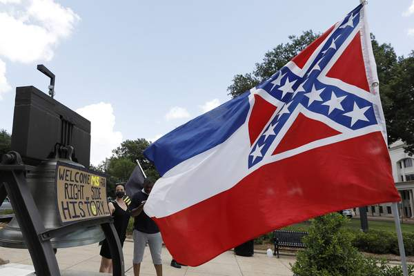 A Mississippi state flag waves adjacent to a flag change supporter's sign that welcomes the state to the right side of history, outside the Capitol in Jackson, Miss., Sunday, June 28, 2020, while lawmakers are expected to consider state flag change legislation. Mississippi Governor Tate Reeves has already said he would sign whatever flag bill the Legislature decides on. (AP Photo/Rogelio V. Solis)