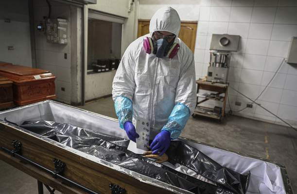 An employee takes the fingerprints of a woman who died from the new coronavirus before her remains are cremated at La Recoleta crematorium in Santiago, Chile, Saturday, June 27, 2020. (AP Photo/Esteban Felix)
