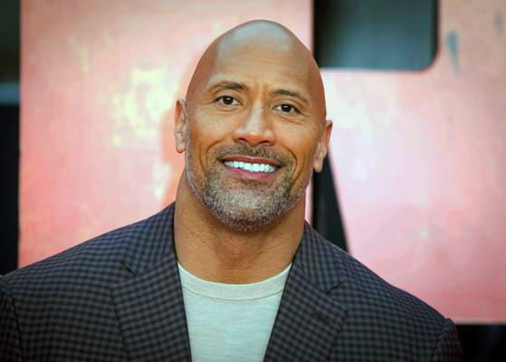 FILE - In this April 11, 2018, file photo, actor Dwayne Johnson poses for photographers at the premiere of the Rampage, in London. Johnson will host and Justin Bieber, Miley Cyrus and Jennifer Hudson will perform on a globally broadcast concert calling on world leaders to make coronavirus tests and treatment available and equitable for all. (Photo by Vianney Le Caer/Invision/AP, File)