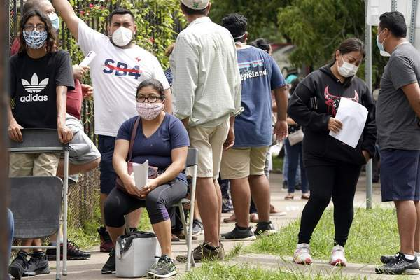 Associated Press  People wait in line at a free COVID-19 testing site provided by United Memorial Medical Center at the Mexican Consulate in Houston on Sunday.