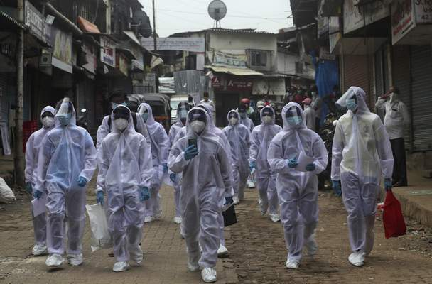 Associated Press  Health workers arrive to administer a medical camp in Mumbai, India, on Sunday.
