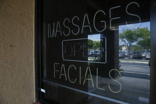 FILE - This March 26, 2019 file photo, shows a sign in the window of the front entrance of the Orchids of Asia Day Spa in Jupiter, Fla. (AP Photo/Brynn Anderson, File)