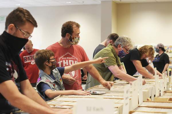 Katie Fyfe | The Journal Gazette  Shoppers rifle through comic books searching for a treasure at the Hobby Show at the Classic Cafe on Hillegas Road on Sunday.