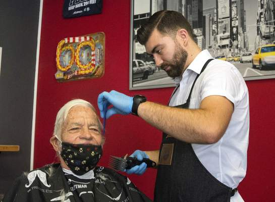 Michelle Davies | The Journal Gazette Tyler Coulson, with Executive Barbershop, gives Dennis Hartmann a free haircut Monday morning inside Big Apple Pizza on Wells Street. The free haircuts were the idea of Marcus Elam to help the community come together and just have fun.