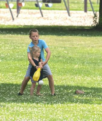 Michelle Davies | The Journal Gazette Henry Baker, 9, of Fort Wayne, helps little sister Marcella, 3, swing the bat during a family game of whiffle ball Monday morning at Lakeside Park.