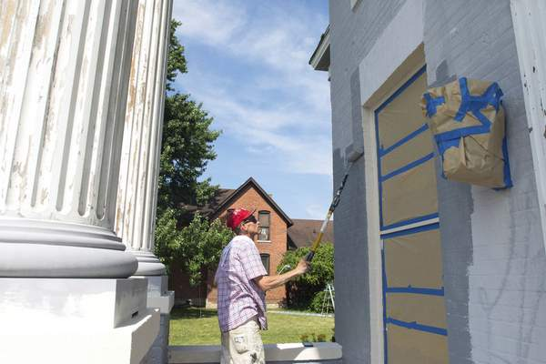 Michelle Davies | The Journal Gazette Bobby Busz, with Tim's Painting, works Monday morning on the historic Hugh McCulloch House on West Superior Street.
