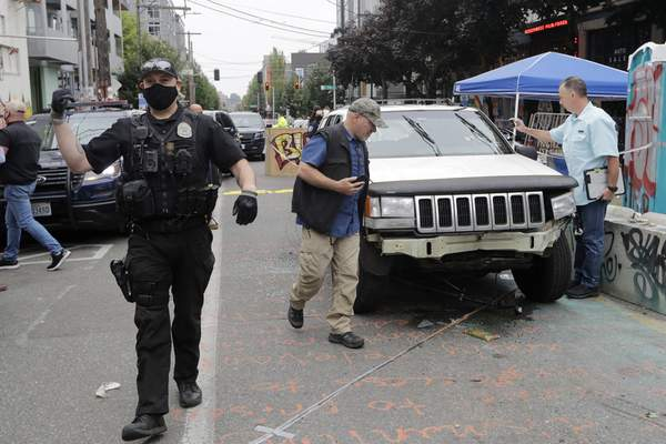Associated Press A Seattle police officer asks people to move aside to allow police vehicles through as investigators look over a car involved in a shooting Monday in a part of the city referred to as the Capitol Hill Occupied Protest zone.