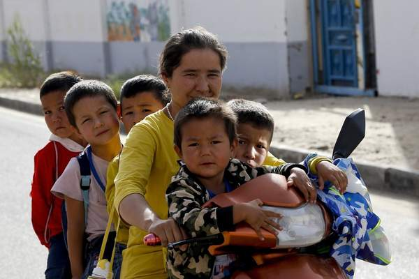 Associated Press A Uighur woman and children sit on a motorbike after school at the Unity New Village in Hotan, in western China's Xinjiang region, in 2018.