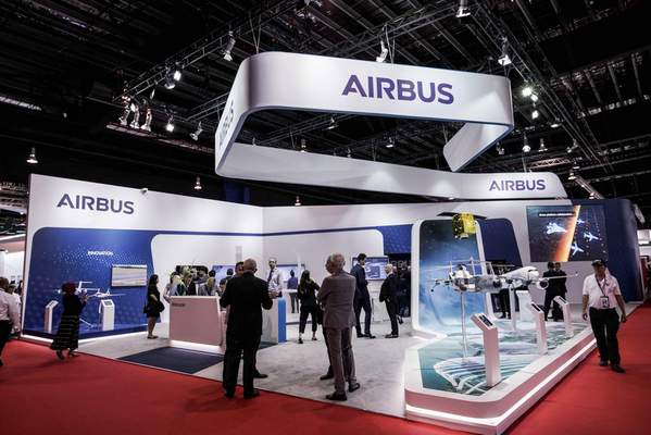 FILE - In this Tuesday, Feb. 11, 2020 file photo, visitors are seen at the booth of Airbus during the opening trade day of the Singapore Airshow 2020 in Singapore. (AP Photo/Danial Hakim, file)