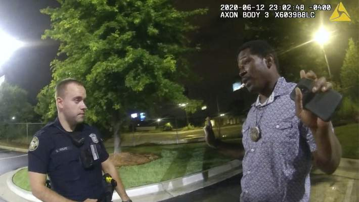 FILE - This screen grab taken from body camera video provided by the Atlanta Police Department shows Rayshard Brooks speaking with Officer Garrett Rolfe, left, in the parking lot of a Wendy's restaurant, late Friday, June 12, 2020, in Atlanta. (Atlanta Police Department via AP)