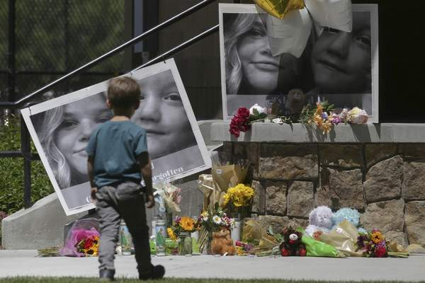 FILE - In this June 11, 2020, file photo, a boy looks at a memorial for Tylee Ryan, 17, and Joshua JJ Vallow, 7, at Porter Park in Rexburg, Idaho. (John Roark/The Idaho Post-Register via AP, File)