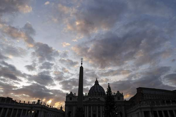 FILE - In this Thursday, Dec. 5, 2019 file photo, the sun sets over St. Peter's Basilica, at the Vatican. (AP Photo/Gregorio Borgia, File)