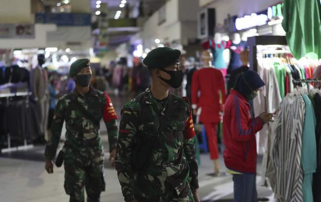 Indonesian soldiers wearing face mask patrol amid fears of the new coronavirus outbreak at a market in Jakarta, Indonesia Tuesday, June 30, 2020.(AP Photo/Achmad Ibrahim)