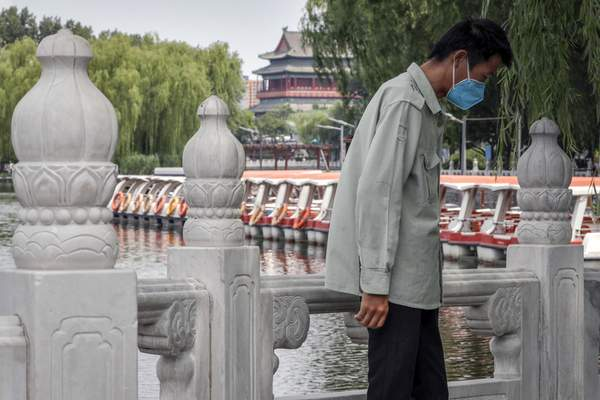 A man wearing a protective face mask to help curb the spread of the coronavirus stands against a roll of boats parked on the barricaded Houhai Lake, a usually popular tourist spot before the new coronavirus outbreak in Beijing, Tuesday, June 30, 2020. (AP Photo/Andy Wong)
